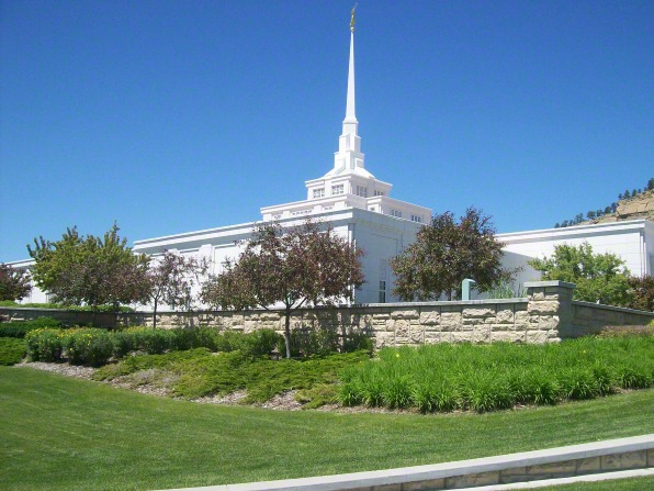 The Billings Montana Temple, seen from the side, with a rock wall and trees in the foreground.