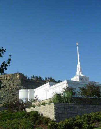 A wide-angle view of the Billings Montana Temple, seen from below, showing the temple's rock wall and the cliffs in the background.