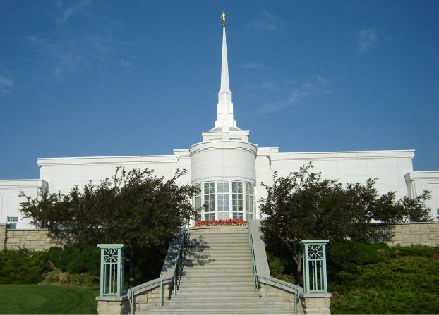 A view of the stairs on the grounds of the Billings Montana Temple leading up to the temple, with green trees on either side of them.