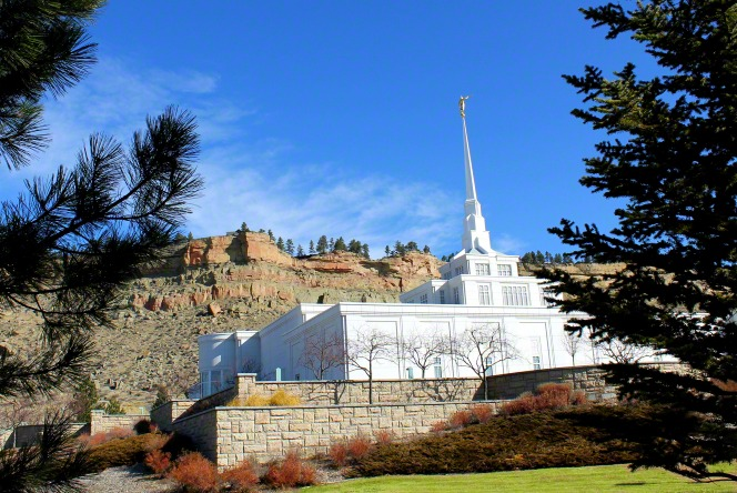 The Billings Montana Temple, with a large rock wall in the foreground and tall cliffs in the background.