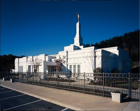 The Birmingham Alabama Temple during the daytime, with the temple's fence surrounding the grounds.