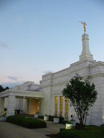 A side view of the entrance to the Birmingham Alabama Temple lit up in the evening.