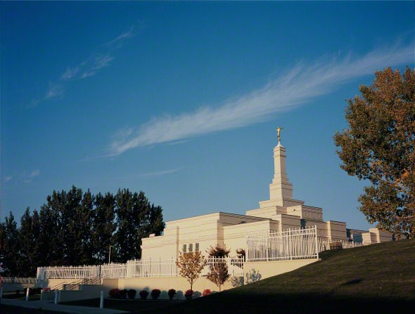 The Bismarck North Dakota Temple, seen beyond a green hill. Trees are also seen in the distance.