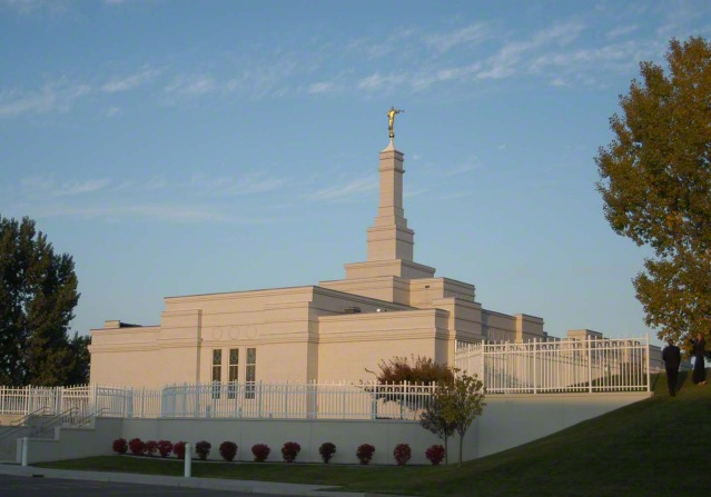 The Bismarck North Dakota Temple exterior in the light of the late afternoon, with two people walking on the grounds in the distance.