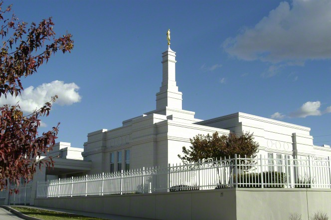 An exterior view of the Bismarck North Dakota Temple during the day, with the temple's white fence around the temple grounds.