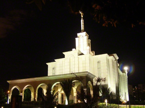A view of the Bogotá Colombia Temple after sunset, lit up against a black sky in the background.