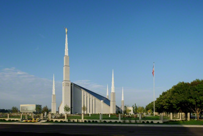 The front of the Boise Idaho Temple as seen from across the street on a sunny day, with the American flag flying on the grounds.