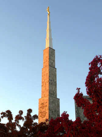 The spire of the Boise Idaho Temple rising above red leaves of fall trees on the temple grounds.