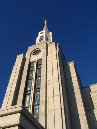 A view of the Boston Massachusetts Temple spire from below, with a blue sky behind it.