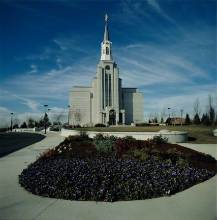 The Boston Massachusetts Temple during the daytime, with a large flower bed in the foreground.