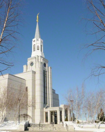 The entrance and spire of the Boston Massachusetts Temple in the winter, with bare trees and snow on the grounds.