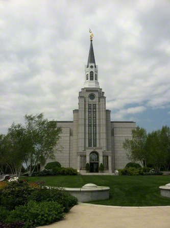 The front of the Boston Massachusetts Temple in the summer, with green grass and trees on the grounds.