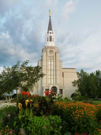 A view of the front of the Boston Massachusetts Temple in the summer, with trees and flowers in the foreground.