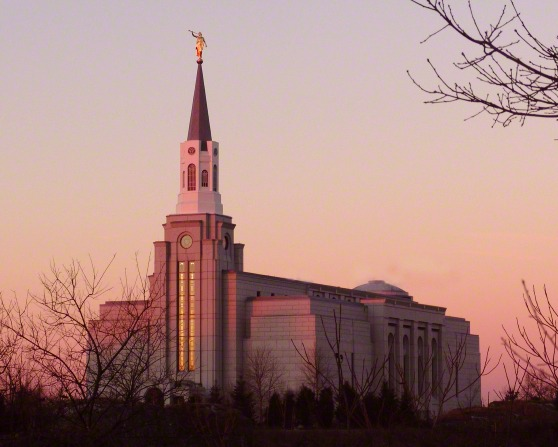 A front side view of the Boston Massachusetts Temple during sunset in the winter, with bare trees on the grounds.