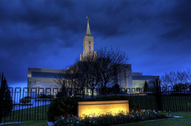 The Bountiful Utah Temple, seen from the bottom of the hill at dusk, with the temple's sign lit up in the foreground.