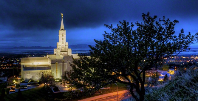A wide-angle view of the Bountiful Utah Temple at night, with the valley lights in the distance.