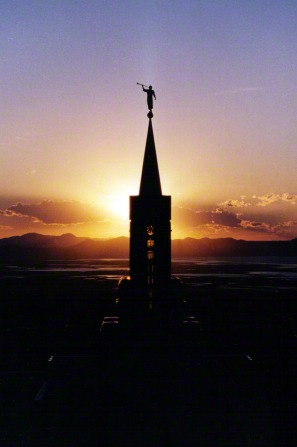 A view of the Bountiful Utah Temple spire, with the angel Moroni silhouetted against an orange sunset in the background.