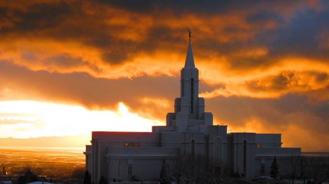 The Bountiful Utah Temple seen from afar, with a yellow and orange sunset in the background.