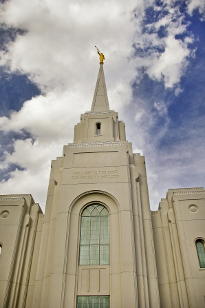 A view of the Brigham City Utah Temple spire as seen from below, with a blue sky and large white clouds.