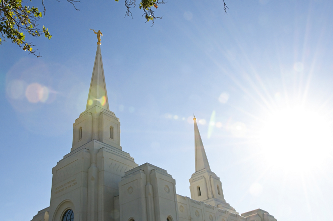 The two spires of the Brigham City Utah Temple seen from below, with the sun behind them.