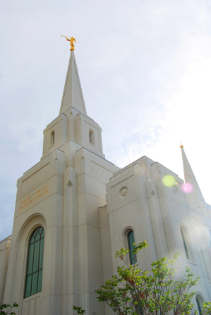 A view of the spires on the Brigham City Utah Temple from below, with a ray of sun on the side.