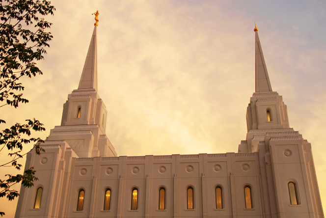 The two spires on top of the Brigham City Utah Temple seen from the side, rising above a row of illuminated windows.