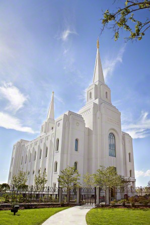 The Brigham City Utah Temple, grounds, and fence on a sunny day, with a blue sky and white clouds.