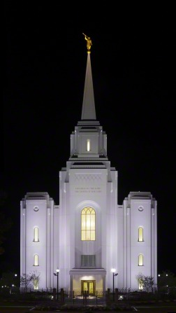 The front of the Brigham City Utah Temple lit up against a black night sky.