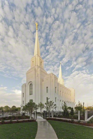 The Brigham City Utah Temple on a sunny day, with small white clouds in the sky.