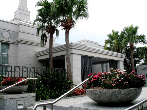 A large stone pot of flowers on the grounds of the Brisbane Australia Temple, with the temple's entrance behind it.