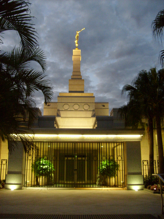 A view of the gated door of the Brisbane Australia Temple lit up at night, with palm trees on the side.