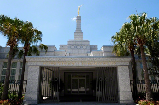 The entrance to the Brisbane Australia Temple, with palm trees on either side and the spire overhead.