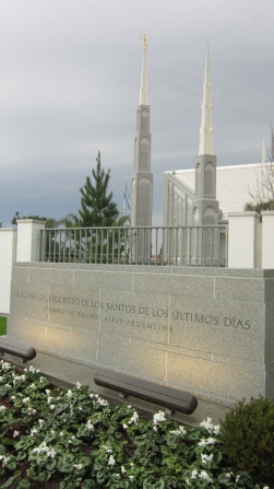 The sign on the grounds of the Buenos Aires Argentina Temple, with the spires of the temple in the background.
