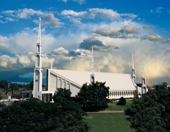 The Buenos Aires Argentina Temple seen from afar, with large green trees in the foreground and white clouds in the background.