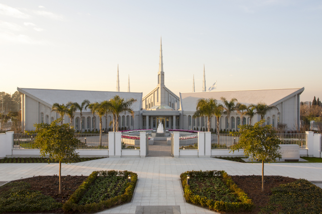 A wide-angle view from afar of the Buenos Aires Argentina Temple in the daylight, with trees and a water fountain.