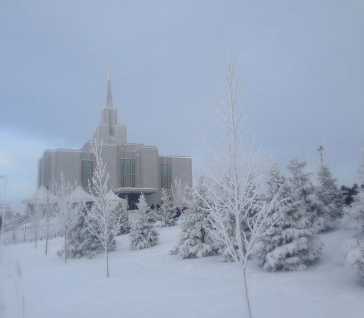The Calgary Alberta Temple and grounds completely covered in snow on a foggy winter day.