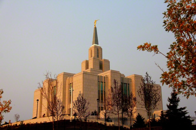 The Calgary Alberta Temple on a fall afternoon, with red trees on the grounds.