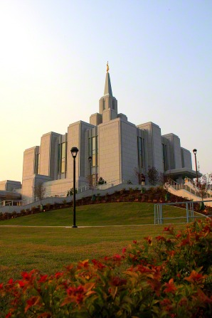 The Calgary Alberta Temple seen from the bottom of the hill, with orange plants and flowers in the foreground.