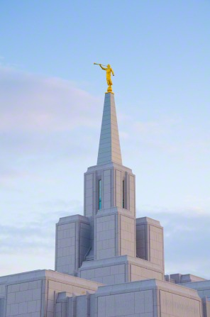 The spire and angel Moroni on top of the Calgary Alberta Temple, with a light blue sky in the background.