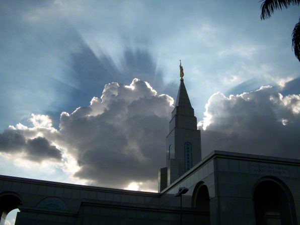 The Campinas Brazil Temple silhouetted against a bright sky, with white clouds and sunshine behind the temple spire.