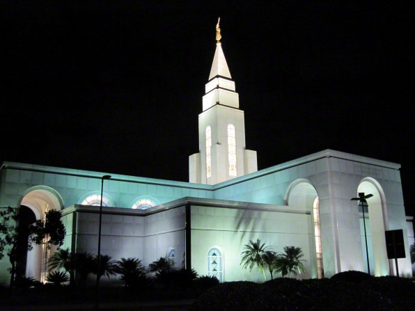 The Campinas Brazil Temple at night, with the lights illuminating it against a black sky.