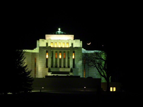 A view of the Cardston Alberta Temple from afar at night, with the lights of the temple on and a small crescent moon in the distance.
