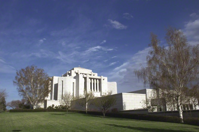 The Cardston Alberta Temple, with the extensive grounds in view and several bare trees on the lawns.