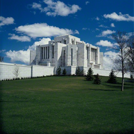 The Cardston Alberta Temple on a green lawn, with several small pine trees in the foreground.