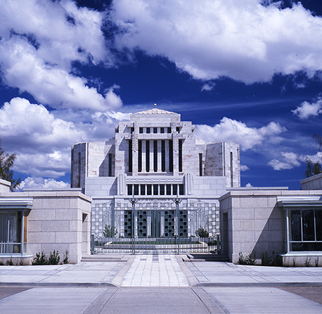 The paved walkways and metal gate leading to the Cardston Alberta Temple, which is seen in full view, with large white clouds in a blue sky.