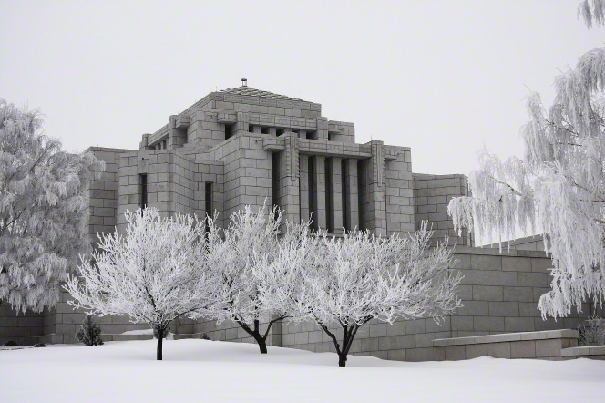The Cardston Alberta Temple in the winter, with snow on the lawns and the trees that surround the temple.