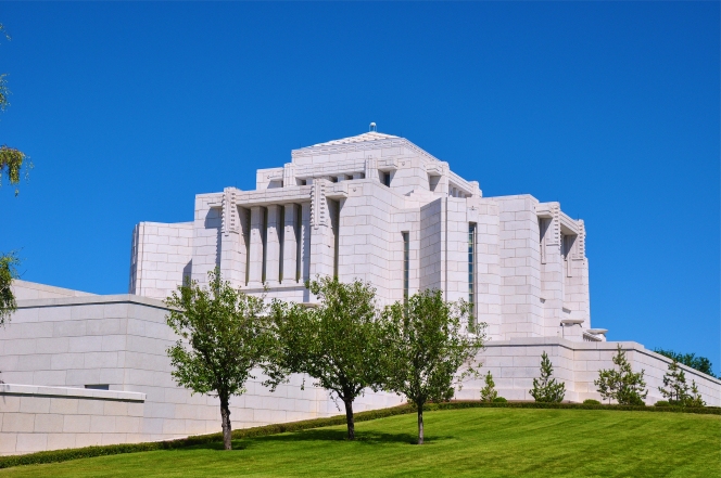 Three green trees on the lawns of the Cardston Alberta Temple, with the temple behind them.
