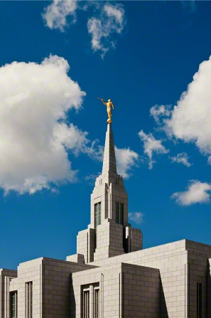 The top half of the Cebu City Philippines Temple, with the spire and angel Moroni set in front of a blue sky with several white clouds.