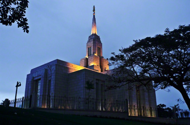 The Cebu City Philippines Temple in the evening, with the lights on in the spire and a large tree on the right-hand side.
