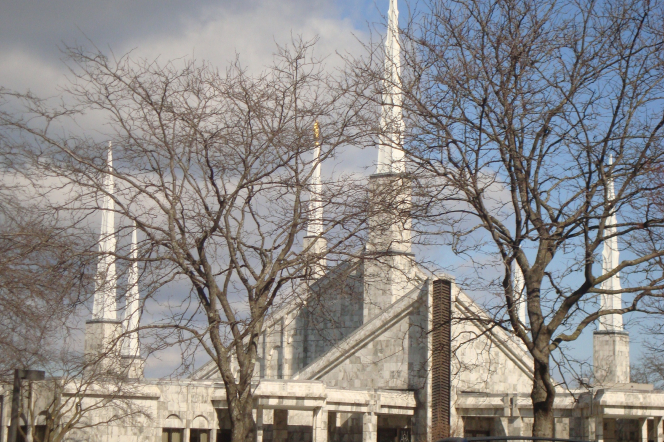 The spires on the Chicago Illinois Temple seen through the branches of bare trees in the winter, with a large gray cloud in the background.